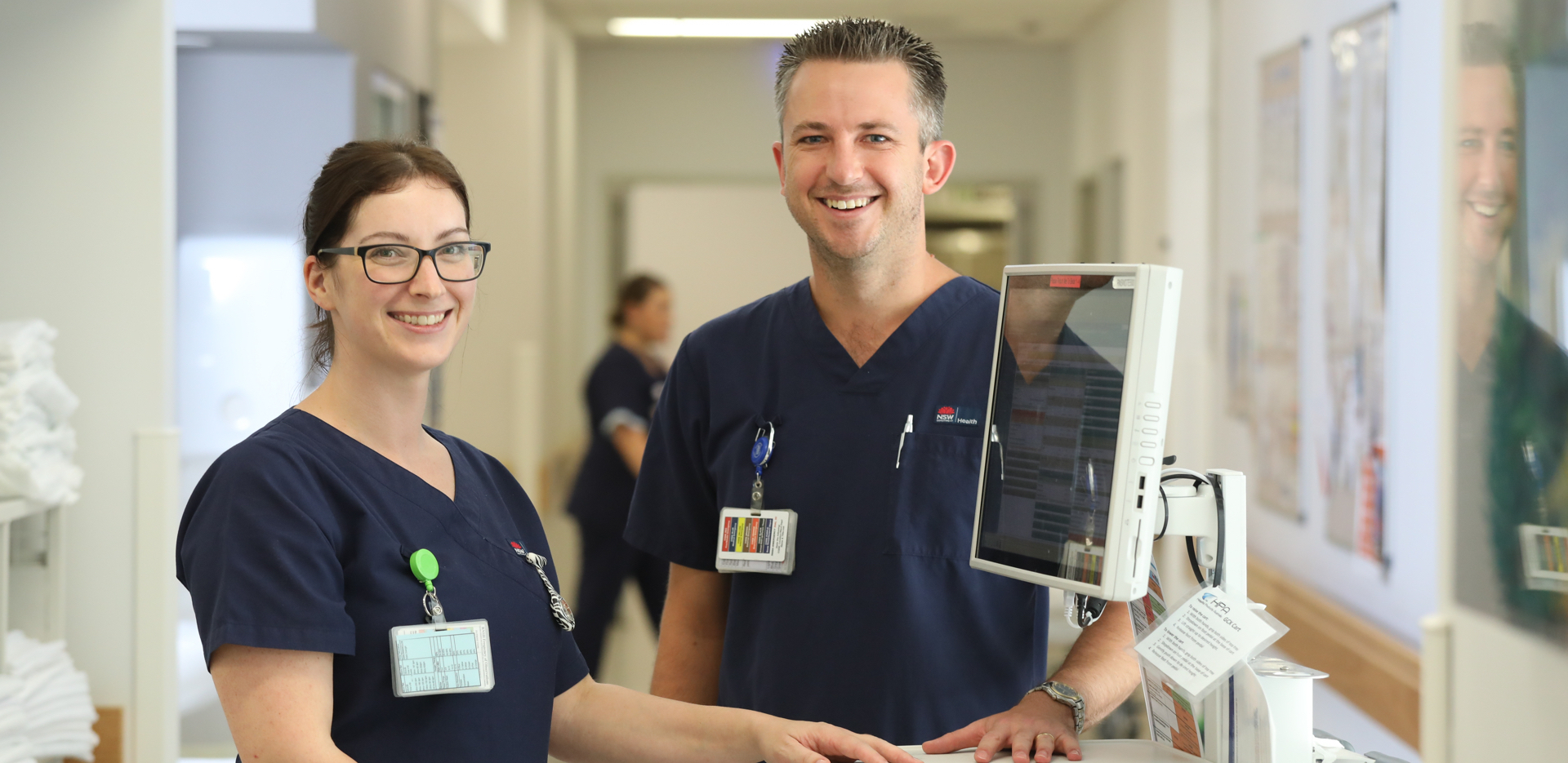 One female and one male clinicans standing in front of a mobile PC.